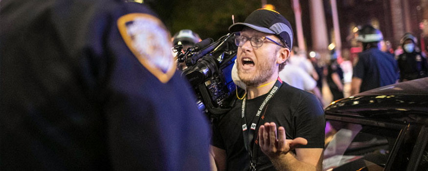 """Associated Press videojournalist Robert Bumsted reminds a police officer that the press are considered """"essential workers"""" and are allowed to be on the streets despite a curfew, Tuesday, June 2, 2020, in New York. Photo: Associated Press"""